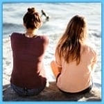 2 grils with their back to us by the sea talking