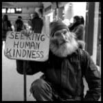 homeless man with a sign says seeking human kindness