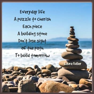 stones stacked on each other with poem build the puzzle of life by laura