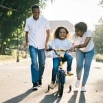 mom and dad teaching their little girl to ride a bike