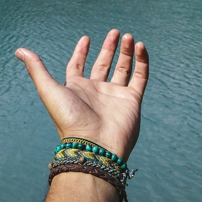hand reaching out over ocean