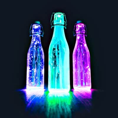 three glass bottles glowing blue, green, purple